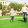 Happy couple running in park — Stock Photo