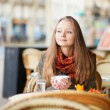 Pensive girl in a Parisian outdoor cafe — Stock Photo