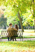 Couple sitting on a bench in park on a spring or fall day — Stock Photo