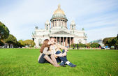 Joyful couple sitting on the grass near St. Isaac — Stock Photo