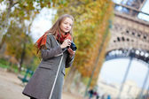 Beautiful girl with photo camera near the Eiffel tower in Paris — Stock Photo