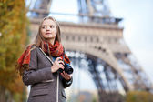 Beautiful girl holding photo camera near the Eiffel tower in Par — Stock Photo