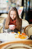 Girl in a cafe with autumn leaves on the table — Stock Photo