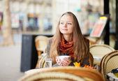 Pensive girl in a Parisian outdoor cafe — Stock Photo
