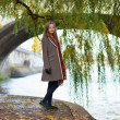 Beautiful young woman near a willow tree — Stock Photo