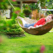 Beautiful woman relaxing in hammock in garden on a tropical reso — Foto de Stock