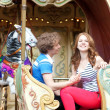 Royalty-Free Stock Photo: Happy young couple in an equipage of vintage Parisian merry-go-r