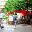 Couple walking in Paris near an outdoor cafe — Stock Photo