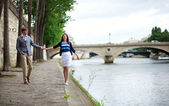 Couple is walking by the Seine embankment in Paris — Stock Photo