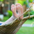 Stock Photo: Womrelaxing in hammock on tropical resort