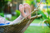 Woman relaxing in hammock on a tropical resort — Stock Photo