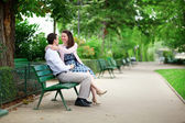 Happy dating couple hugging on a bench in a Parisian park — Stock Photo