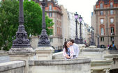 Dating couple is kissing tenderly in Paris on a bridge — Stock Photo