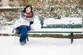 Hermosa chica sonriente con un pequeño muñeco de nieve — Foto de Stock