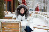 Beautiful girl in fur hood sitting in an outdoor cafe on a winte — Stock Photo