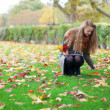Young girl gathering bright autumn leaves — Stock Photo