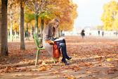 Girl reading in park on a fall day — Stock Photo