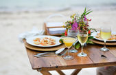 Romantic dinner served for two on a beach — Stock fotografie