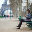 Stock Photo: Girl sending sms or surfing in the net in Paris