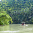 Outrigger boat on a tropical river — Stock Photo