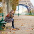 Girl sitting on a bench on a fall day — Stock Photo