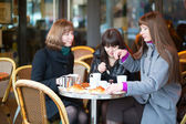 Friends in a Parisian street cafe, chatting — Stock Photo