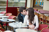 Young couple kissing in an outdoor cafe — Stock Photo