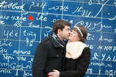 Couple kissing across the I Love You wall in Paris — Stock Photo