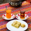 Orange and apple Turkish tea served with baklawa - Stock Photo