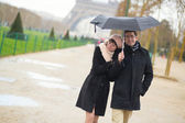 Couple in Paris under umbrella — Stockfoto
