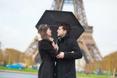 Couple with umbrella near the Eiffel tower — Stock Photo