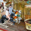 Couple having fun on a merry-go-round - Stock Photo
