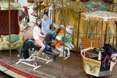 Couple having fun on a merry-go-round — Stock Photo