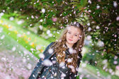 Girl under falling pink petals on a spring day — Stock Photo