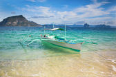 Outrigger boat on a perfect tropical beach — Stock Photo