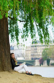 Girl reading under a tree in Paris — Stock Photo