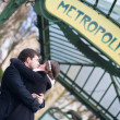 Couple kissing under the metro sign in Paris — Stock Photo