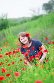 Smiling girl in a poppy meadow — Stock Photo