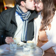 Dating couple kissing in a Parisian cafe — Stock Photo #25901689