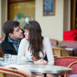Dating couple kissing in a Parisian cafe — Stock Photo #25902223
