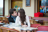 Dating couple kissing in a Parisian cafe — Stock Photo