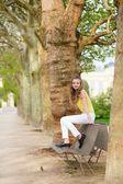 девочка сидит на скамейке в парке — Стоковое фото