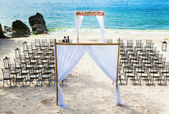 Wedding arch and chairs on the beach — Stock Photo