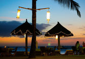 Beach umbrellas and lanterns during sunset — Stock Photo