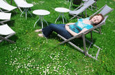 Girl relaxing in chaise longue on a summer day — Stock Photo