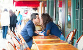 Couple kissing in an outdoor cafe — Stock Photo