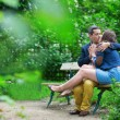 Young loving couple kissing on a bench — Stock Photo
