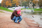 Mother and daughter together on beach by fall — Stock Photo