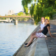 Couple relaxing on the bank of the Seine — Stock Photo