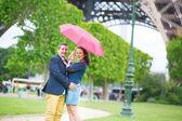 Para pod czerwony parasol w paryżu — Zdjęcie stockowe